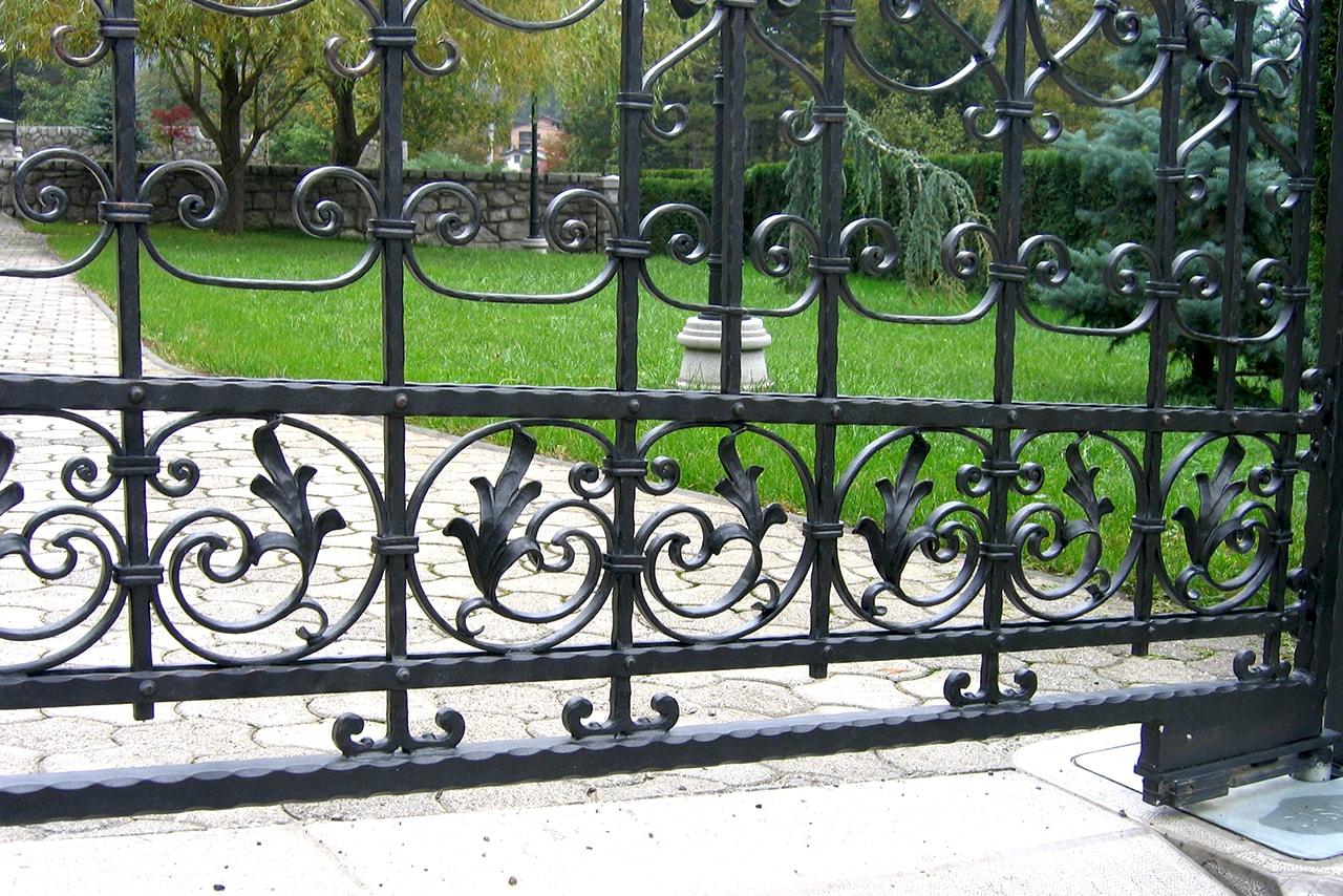 Dvoriščna vrata s simbolom narave in električnim odpiralnim sistemom.