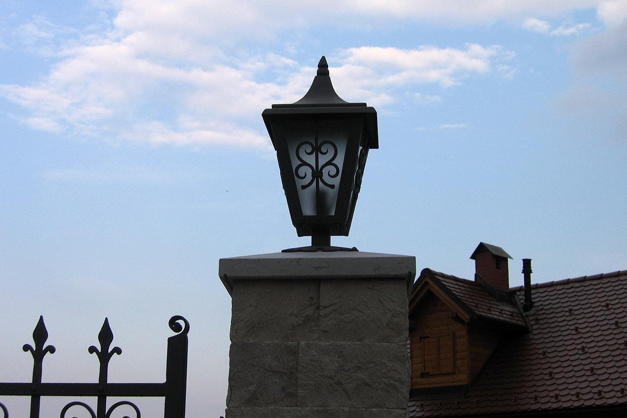 Kovana svetila nameščena na vrtno ograjo
